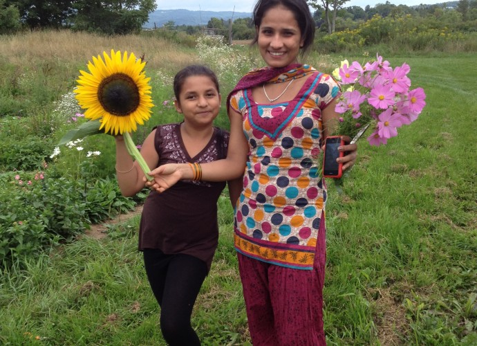 Old Path Farm, a nearby organic farm in Sauquoit, NY, has welcomed refugees to participate in planting, harvesting, cider-making, and other activities throughout the year. In this photo, Pisanti Adhikari and Sabitra Acharya show off the flower bouquets they picked for their mothers. June, 2012. Photographer: Kathryn Stam.