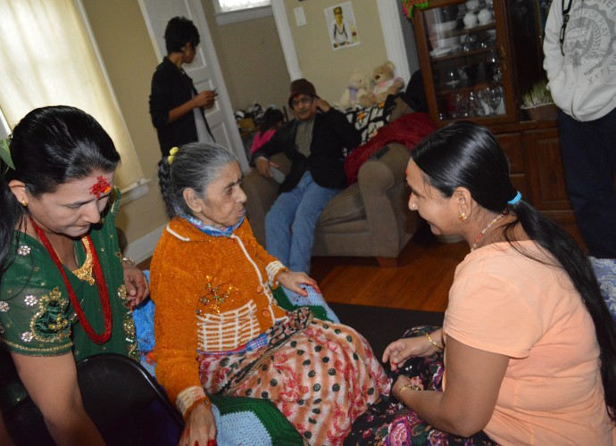 """During important days for Hindus, it is still important to visit elders and request that they give a """"tikka"""" (red paste with rice placed on forehead) and a blessing. Nov. 2013. Photographer: Krishna Adhikari."""