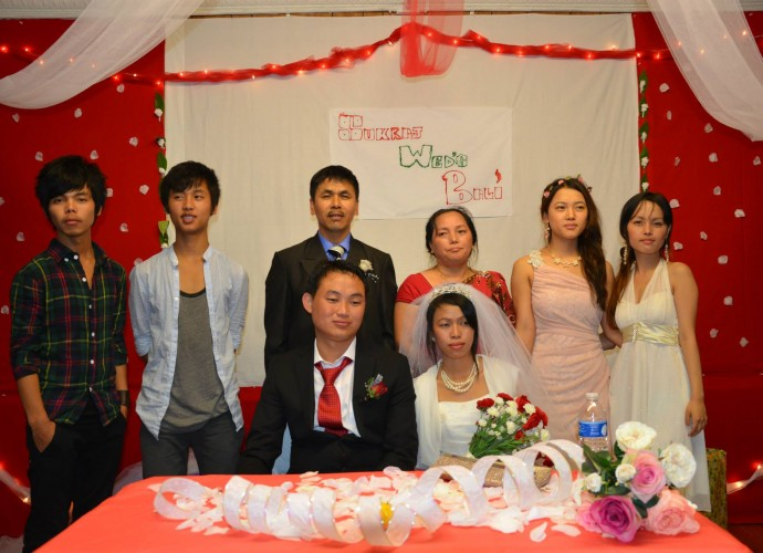 This photograph was taken at the Christian wedding reception of Sukraj and Bali Rai. Some of the Bhutanese-Nepali refugees in Utica, NY have maintained their Hindu or Buddhist faiths while the others have converted to Christianity. The Christians attend a local non-denominational church. They also maintain the tradition in which the bride goes to live with the groom, in this case a Utica resident. Nov. 2013. Photographer: Tek Monger.