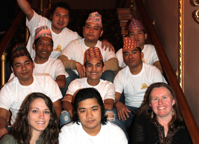 Authors Katie Reilly and Kathryn Stam pose here with Santa Rai and other members of the Bhutanese-Nepali Folk Collective, including coauthor of this piece Mon Ranamagar (upper right). The band, which includes traditional and popular dancers as well, was formed in December 2012 and has performed many times since then at cultural fairs and local colleges. The band plays traditional folk songs in Nepali language, and aims to maintain their cultural traditions and ideas for the sake of their community. April, 2013. Photographer: Krishna Adhikari.