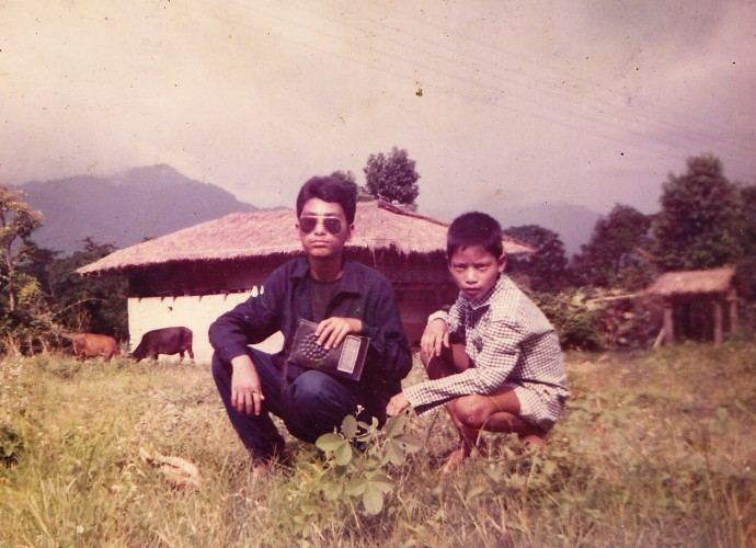 "Amber Ranamagar (Left, also from the previous photo) is pictured here with his brother Harka in front of their home in Gelephu, Southern Bhutan, where they lived with their family until they were evicted from their land and their citizenship was revoked by the Bhutanese government in 1992. According to many Bhutanese-Nepali refugees who remember their lives before the conflict, southern Bhutan was a pleasant place with natural beauty and where they appreciated their good health, education, and productive agriculture. Some refugees find it ironic that the Bhutanese government is well known for its ""Gross National Happiness,"" policy but not for the political conflict and eviction of 100,000, ""Lhotshampas,"" or ethnic Nepalis living in the South of Bhutan. Photographer: Unavailable. Permission to publish from Mon Ranamagar."