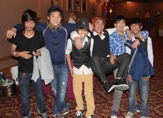 Bhutanese-Nepali teens enjoy themselves after a Nepali cultural performance at Culturefest on April 13, 2013 at the Stanley Theater in Utica, NY. These college and high school boys were all born in Nepal while their families were living in Beldangi 3 refugee camp in Eastern Nepal. They feel comfortable in native and Western dress, and are known in part for how frequently their change their hair color and style. Govinda Adhikari (far left), and his family were the first Bhutanese-Nepali family to be resettled in Utica, NY. Also pictured (from left to right) are Eshek Rai, Nava Adhikari, Krishna Adhikari, Rakesh Baniya and Anil Dharjee. Photographer:  Katie Reilly.
