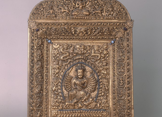 <p>Votive plaque featuring Durga <br /> Nepal <br /> 18th century <br /> Courtesy of National Museums Liverpool, 53.87.54<p>  <p>This devotional plaque which features Durga is made from wood, covered with copper gilt and fitted with turquoise and precious stones. The quality suggests it was made for a wealthy Hindu devotee. It is fitted with <em>vajra</em> (Tib. rdo rje, a ritual object that symbolises the properties of the thunderbolt and the diamond – the Sanskrit meaning of <em> vajra</em>) recognised by Hindus, Jains and Buddhists. The inclusion of the <em> vajra</em> makes the cultural and religious exchange of ideas and practice visible. But there is another possible story that the plaque has yet to tell. This one reflects the practice of museum curation and the museum curator's interest in reconnecting objects to their biographical record and the relationships they once had to people and events. In this case, the unsolved clue comes in the form of a collector's name noted on the object's museum label. The collector/owner of the plaque was Sir Charles James Stevenson-Moore (1866-1947) an Indian Civil Service officer. From 1904-07 he was the Inspector General of the Bengali Police force, responsible for the security detail that watched over the ninth Panchen Lama, Thupten Chökyi Nyima (1883-1937) during his visit to Calcutta in 1905-06. Was this high status item then one of the gifts that the Panchen Lama brought to Calcutta for the British Indian government. (Gifts given by dignitaries from across the Himalayan and wider Asian worlds were often stored in specific gift treasuries in Tibet so that they could be given again to unconnected dignitaries at future diplomatic meetings). Had Stevenson-Moore subsequently bought it at auction or from the British India Treasury when the Tibetan gifts were sold off? Had this plaque criss-crossed the Himalaya during its devotional life? This is just one of many hundreds of object biographies still to be uncovered. </p>