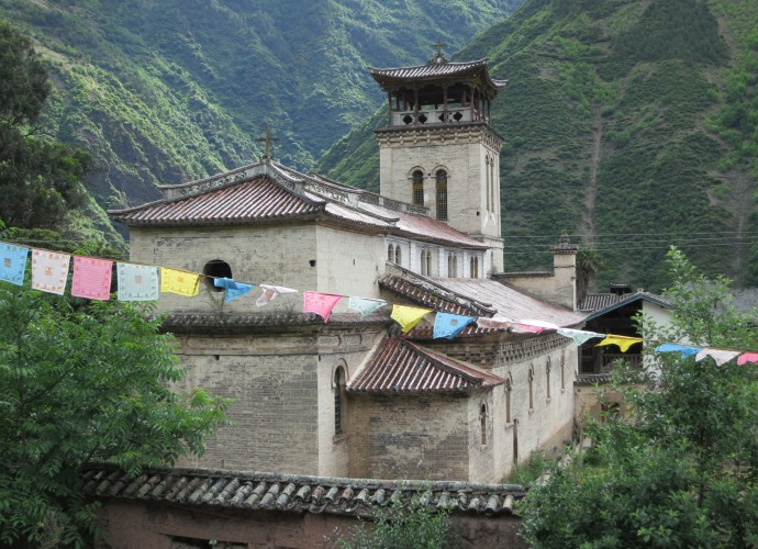 <b><p>Cizhong Church built in 1909.</b></p> Wine in Cizhong village is made of grapes, primarily from a variety known as 'Rose Honey' that was introduced to the Tibetan areas of Yunnan Province by French and Swiss Catholic missionaries over a century ago. This <em>Vitis</em> cultivar is thought to contain at least some DNA from the species <em>vinifera</em> hybridized with other unconfirmed species, though its definitive origin is still unknown.  Assumed to be of missionary introduction and previously grown in Europe, it was wiped out by a blight and earlier thought to be extinct (Dangl 2011). By a twist of fate it still exists, but only in Yunnan Province (Galipeau 2015).