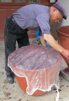 <b><p>Sealing the crushed grape juice, seeds, and skin for fermentation.</b></p>