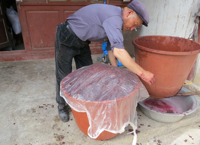 <b><p>Sealing the crushed grape juice, seeds, and skin for fermentation.</b></p> After crushing the leftover stems are picked out of the basins, leaving the grape juice and sediments of grape skins and seeds, which are poured into large plastic buckets.