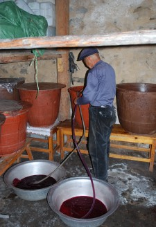 <b><p>Pumping the fermented wine from the barrel containing sediments of grape seeds and skin.</b></p> In order to filter the wine it is siphoned out into small basins or barrels from the larger buckets using a plastic tube. Any leftover grape skins and seeds sieved out are also saved and stored in a bucket for later grape liquor distillation. The filtered wine is then poured back into the buckets and sealed tightly with plastic film again to ferment.