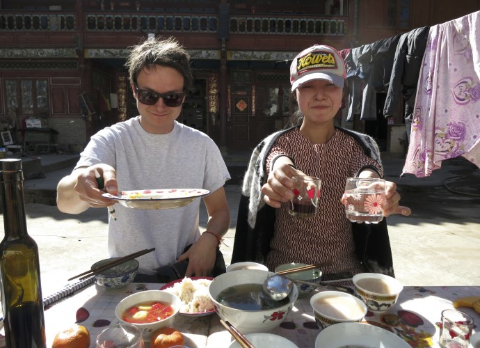 <b>Tourists entertained by Hongxing as he proudly served his wine.</b>