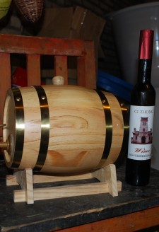 <b><p>Wu Gongdi's and his son Hongxing's wine in a barrel and a Cizhong labeled bottle.</b></p> Most households in Cizhong produce relatively small amounts of wine compared to Wu Gongdi and only sell to visitors and also sell some grapes to the local Shangri-La Wine Company. The Shangri-La Wine Company is a recent development throughout the lowland river valleys of Deqin County where Cizhong is located. Developed in the early 2000's by the local government as a poverty alleviation scheme, the company and the county government have promoted the conversion of traditional agricultural fields of barley and wheat throughout Deqin into monocroped vineyards. In most villages the grapes produced in these vineyards are sold directly to the company for winemaking rather than being used for household winemaking as they are in Cizhong. While the growing of grapes has overall led to higher annual incomes for households throughout the region, there have been drawbacks in terms of sustainability and food security. Having abandoned the production of grains for subsistence consumption, households are reliant on the sale of grapes to purchase food, and the Shangri-La Wine company does not have guaranteed contracts with villagers from one year to the next, often showing up late to purchase grapes after they have ripened and begun to dry out. In addition, the grapes introduced to Cizhong more recently and to other villages by the government and the company are of a different Cabernet variety, which requires heavy use of chemical pesticides and fertilizers. For more detailed information and these agricultural transformations in Deqin County associated with viticulture, see (Galipeau 2015).