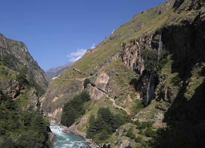 Kermi to Dharapori road section, October 2017.  Arguably one of the most dramatic sections of the Hilsa – Simikot route, the Chachara cliff overlooks the Karnali river below to form the base of Chaduk, a village located directly overhead. The streams from the village drop over 200 meters below forming a picturesque waterfall. The cliff is approximately a kilometer in length and forms the biggest hurdle in completing the road and reaching the district headquarters of Simikot. Reportedly, the explosives necessary to sculpt the cliff are not available in Nepal. The Nepal Army (NA) has been called in to undertake the task, but it might be years before this work is completed. Because of the cliff, people in Kermi believe that a major road head market might come up near Kermi. Currently, there are only three small tea shops each in the north and south of Kermi, but none in the village.