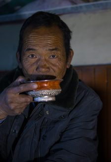 Norbu. (Kory Thibeault, October 2016)  Norbu is a renowned community leader and politician. This photo was taken after a long day working in his apple orchards near the village of Kagbeni. He enjoys a hot butter tea while recounting stories of his life and old customs of the region.