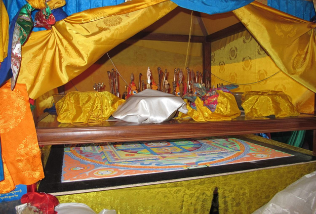 All the vessels are placed on a sheet of glass right above the mandala along with various offerings to the deities invoked. In the photograph, the white vessel of the Centre and the yellow vessels of the intermediate points can be seen. The five-colored 'spell cord' strings lead from the mandala to the throne of the presiding performer of the ritual, the abbot of the monastery. The cord transmits the powers and blessings of the deities summoned by the practitioners to the mendrup mandala and into the medicine.