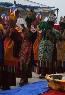 On the fifth day of the fifteen days-long-ritual action, the Eight Goddesses carry the mendrup medicine vessels out of the mandala and the assembly hall to perform the grinding of the medicine. The procession is led by an honorable monk carrying the precious container of the papta (phabs gta') or 'fermenting agent,' which is wrapped in yellow cloth. He is then succeeded by a monk carrying the white vessel of the Centre, followed by the vessels of the East, North, West, and South, according to the Bonpo anticlockwise order. Then come the vessels of the intermediate cardinal directions (Northeast, Northwest, Southwest, and Southeast). Since all of them are in yellow color, their sequence is not distinguishable. The large metal container visible in the front is ready for grinding.