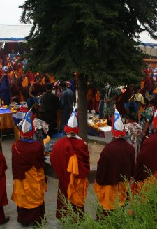 A scene from the ritual grinding of the mendrup medicine. Amchi Nyima and his main disciple Namsé (Gnam gsas, also Gnam sras) are standing in the centre (under the tree) and pour the contents of the medicinal vessels into a mortar. All members of the congregation symbolically take part in the task and beat the substances three times with a pestle. Despite the high number of participants, most of the hard work is done by Amchi Nyima and Namsé.