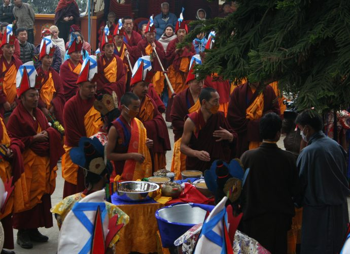 The medicinal vessels containing ground and unground ingredients are laid out on the table in front of Amchi Nyima (second from right) and Namsé (right). Monks accompany the act with ritual music and recitations.