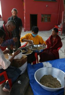 The ritual grinding of the mendrup medicine continues until late afternoon. Amchi Nyima (second from right) and Namsé (far left, in white shirt) direct the mendrup participants in beating the mendrup medicine in the mortar. A visiting practitioner from Himalayan Bonpo communities is just taking part at the pestle (second from left), being watched by a Western Bonpo follower who has already had his turn (third from left). Amchi Nyima pours the raw ingredients into the mortar with a ladle. He then sieves the ground mixture so that only fine powder constitutes the final empowered mendrup medicine. A young monk (first from right) keeps them company during the grinding. Once the grinding is completed, the mendrup medicine is returned to the mandala of the ritual in the center of the assembly hall.
