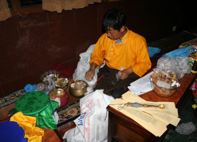 Amchi Nyima is mixing the raw ingredients and filling the cardinal medicinal vessels to be placed upon the mendrup mandala during the ritual. He closely follows the photocopied manuscript of the mendrup medicinal formula which lists more than one hundred ingredients and is placed on the table in front of him. Amchi Nyima is including all of those herbal ingredients that he can comprehend from the formula, as well as a few minerals and one animal substance (red lac). Nevertheless, he skips the part of the recipe listing animal and human body parts. The colorful ritual 'spell cord' (byang thag, gzungs thag) is wrapped around a ceremonial brass ladle. The spell cord has five strings in the five colors of the cardinal directions. The cord connects the abbot presiding over the ritual with each point on the mandala and its medicinal vessel (see below). The ladle will be used for liquid offerings to the deities invoked.