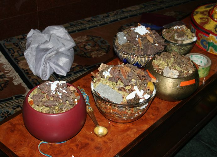 The vessels of the five cardinal points are filled with raw medicinal ingredients. The photograph shows some of them: white sugar (ka ra, one of the 'three sweet [substances],' mngar gsum), kaolin (cu gang), safflower (bal gur gum), cinnamon, as well as smaller (sug smel) and greater cardamom (ka ko la). A few ingredients, such as the 'three sweet [substances]' and cinnamon visible here, were included as additional substances according to the oral instructions of Yongdzin Rinpoche. They are not found in the mendrup recipe.
