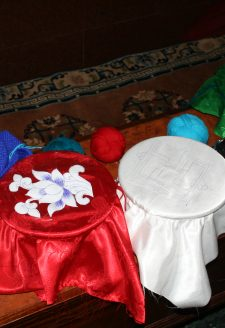 The medicinal vessels of the five cardinal points are covered with cloth lids of their respective signs and colors: the white cloth with a swastika will occupy the Centre, the green with a dharma wheel the North, the red embellished with a lotus flower will represent the West, and the blue with a flaming jewel the South. The yellow cloth covered bowl representing the East is missing in the photograph.