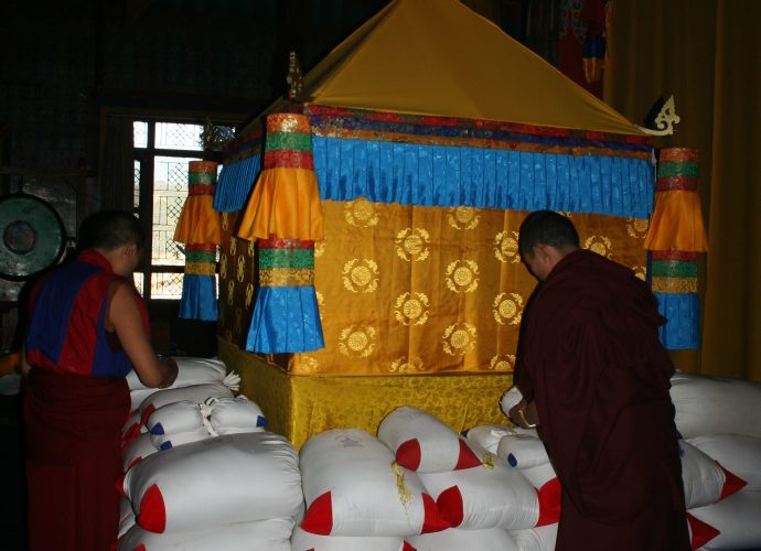 All the mendrup medicine bags are then arranged around and below the special ritual structure containing the mendrup mandala. The structure is of yellow color. Here, the blue color of the cardinal direction of the South is visible, as well as some of the red color of the West. Monks are organizing the small and large bags of the mendrup medicine around the mandala.