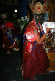 Once the mandala is installed at the centre of the main assembly hall of the monastery, its structure is sealed and forbidden to be opened. The 'Eight Goddesses,' played by young monks dressed as goddesses, perform a vivid dance in the Bonpo anticlockwise direction around the mandala, during which they place the mendrup medicinal vessels on the mandala. In the front appears the 'Goddess' holding the white bowl representing the Centre.