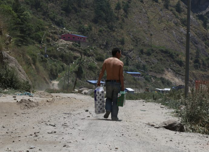 A Chinese worker carrying toilet paper and a box of Lhasa beer to Rasuwagadhi hydropower construction site, Rasuwa. A sizable number of Chinese workers are employed at the hydroprojects in Rasuwa, where they are considered more skilled than Nepalese workers who work alongside them. Unsurprisingly, the residents say the pay gap between the Chinese and Nepalese is quite high, with Nepali workers receiving far less compensation than their Chinese counterpart.