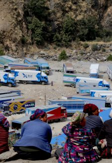 A group of local women working as porters at the border overlook a truck parking lot at Timure. A large number of local residents currently work in Timure truck park where they transport imported good after they clear customs. They are mostly from  Timure, but also include locals from neighboring villages such as Thuman, Khangjim, Bhirdim, Chilime, Gatlang, among others. There are also people from outside Rasuwa district who work as porters in Timure. According to one of our interlocutors, Timure truck park employs the greatest number of locals from the region despite the hard work it requires. Often, locals from the neighboring villages rent a small room in Timure during the peak season when it is more profitable. The majority of the people working in the park are primarily women, and toddlers can often be seen playing around as their mothers move goods.