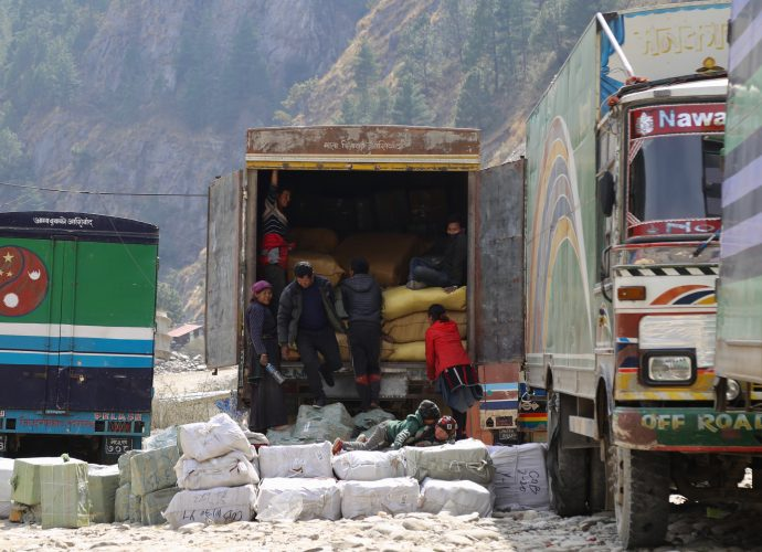 Porters unloading goods from a truck at Timure parking for customs clearance, Timure. In Timure, a large number of residents work in the parking area to load and unload imported goods from China that make it through customs. On a working day, hundreds of porters can be seen loading goods onto Nepalese trucks at the border. Depending on the season, a group consisting of five to six porters earn NRs 5000-8000 per day (roughly 44-70 $USD). According the residents, those working as porters at parking can earn between NRs 50,000-60,000 (roughly 445-530 $USD) during peaking season.